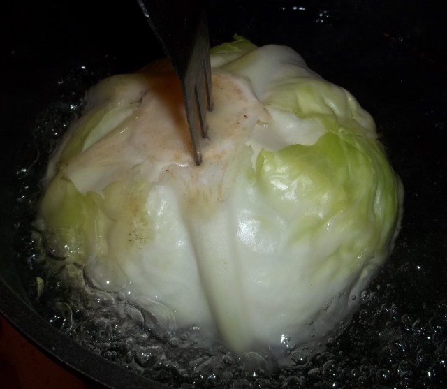 holding-the-cabbage-in-boiling-water-for-nuts in cabbage leaves-recipe
