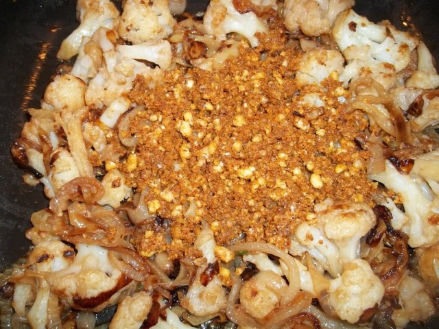 Adding Crushed Ingredients to Fried Cauliflower and Onions