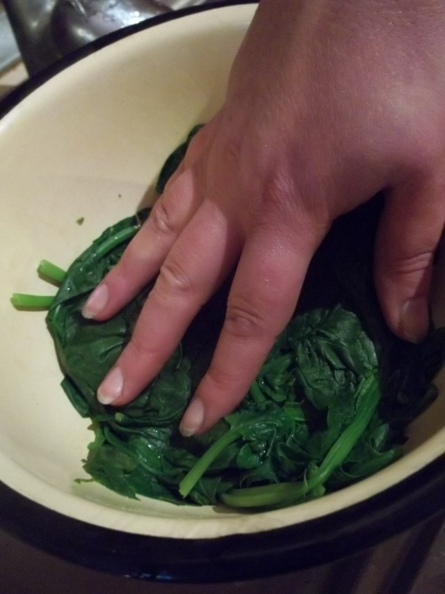 Using a Colander to Drain Cooked Spinach Leaves