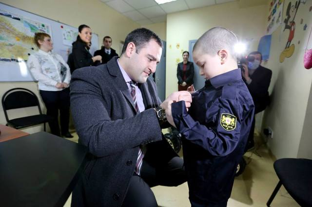 The Interior Minister, Alexander Chikaidze, presents a specially tailored patrol police uniform to one of the boys
