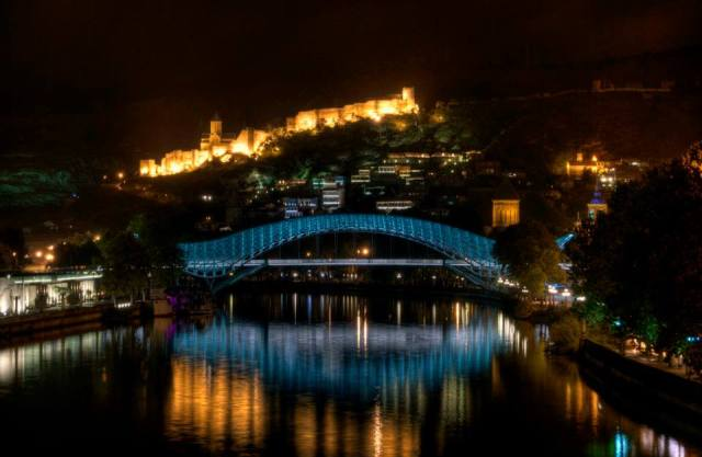 Tbilisi's Bridge of Peace and Narikala Castle illuminated at night