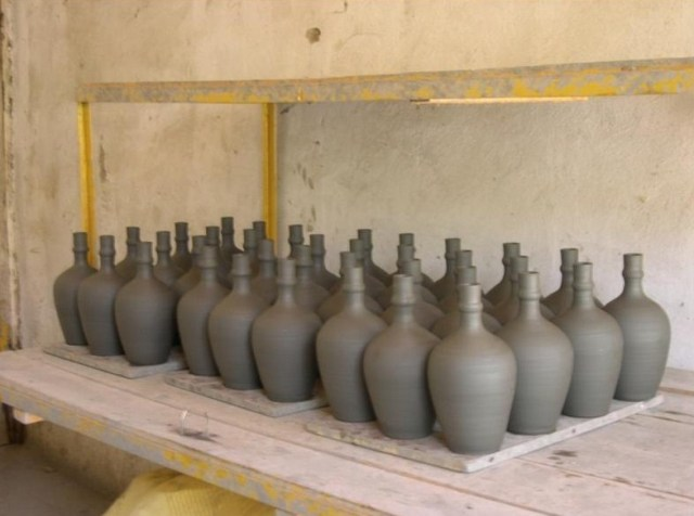 Ceramic wine bottles before artwork and firing.