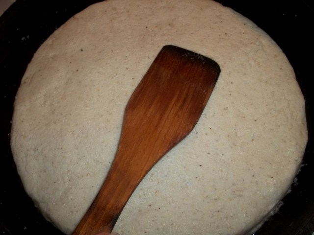 Using a wooden spatula to smooth the surface
