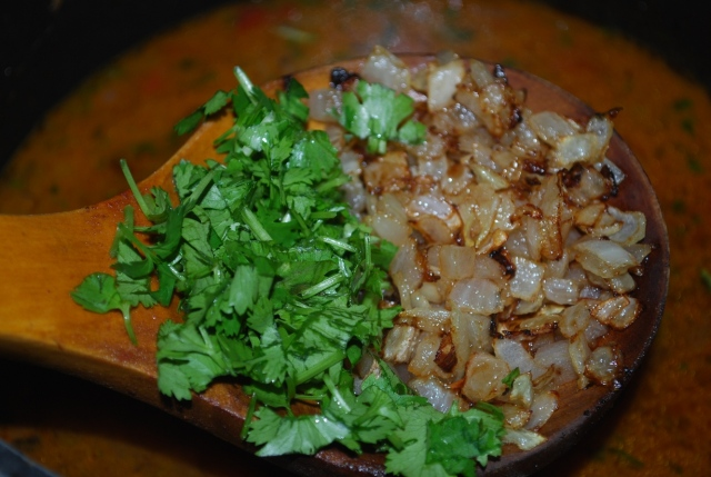Adding Coriander and fried onions to boiled lobio