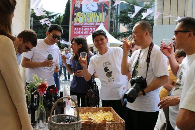 Tourists tasting wine at an event to mark Georgian Wine Day